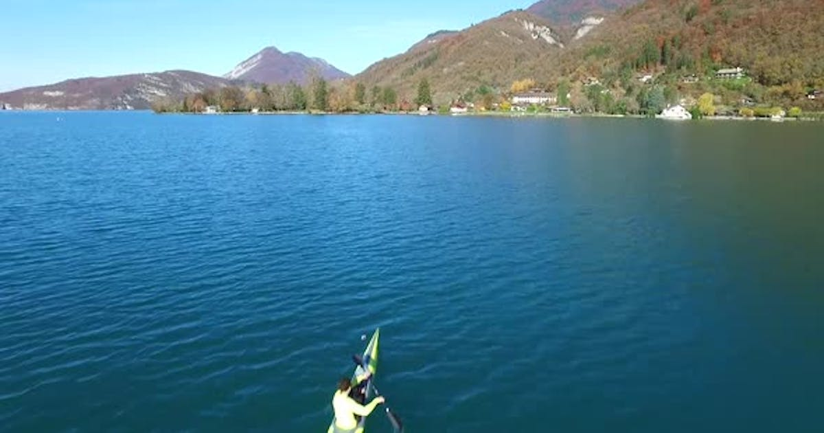 A kayaker paddles in a scenic mountain lake.