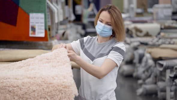 A Young Woman Wearing a Protective Mask at a Home Goods Store. The Girl Chooses a Carpet in Her