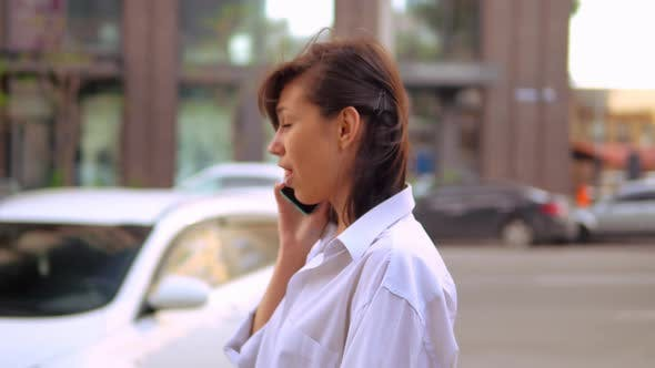 Thumbnail for Side View Close Up Young Businesswoman Talking By Phone Walks Along Road