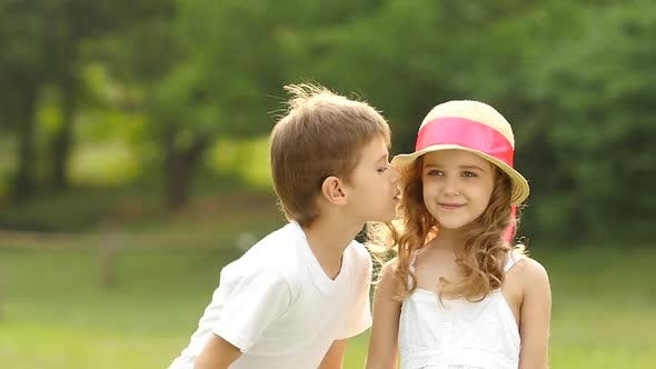 Thumbnail for Little Boy Kisses the Girl on the Cheek, She Is Embarrassed and Smiles. Slow Motion