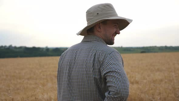 Thumbnail for Rear View of Young Agronomist Standing at Wheat Meadow, Turning To Camera and Laughing. Male Farmer