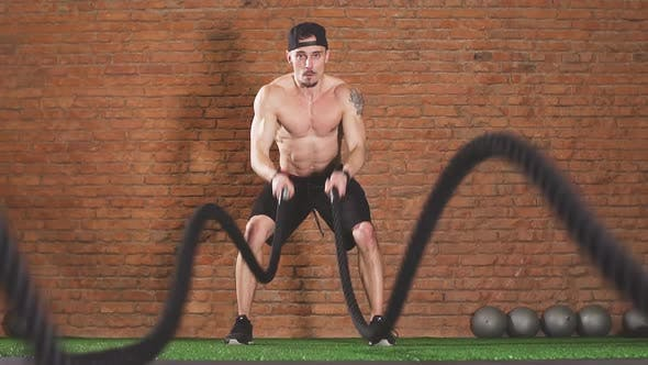 Thumbnail for Determined Male Athlete Performing Waves By Battle Rope, in Crossfit Club, Slow Motion