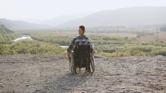 Man in Wheelchair with Great Willpower Celebrating Ascent on the Top of Hill with Raised Arms