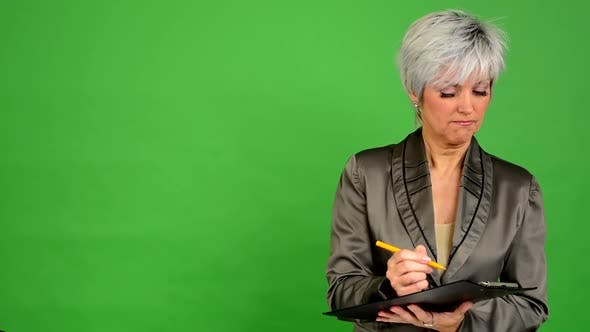 Thumbnail for Business Middle Aged Woman Writes To Paper and Smiles To Camera - Green Screen - Studio