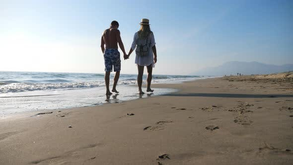 Thumbnail for Couple of Lovers Walking at Seashore Holding Hands During Recreation on Resort. Man and Woman