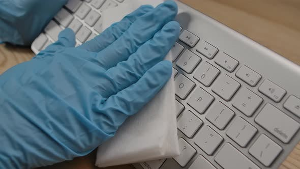 Thumbnail for Man in Protective Gloves Cleaning Keyboard Surface with Alcohol Disinfectant and Removing Dirty with