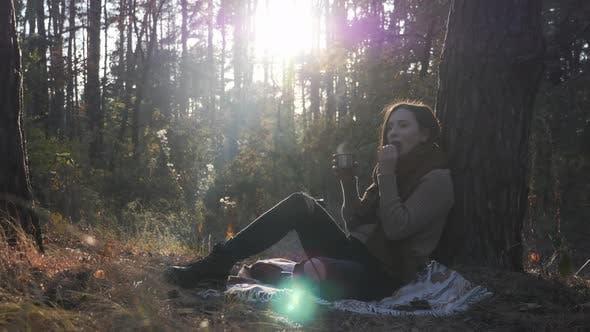 Thumbnail for Glückliche junge Frau Touristen trinken heißen Tee und essen Kekse entspannen im Herbst Wald bei Sonnenuntergang