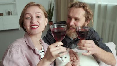Caucasian Family Bearded Man and Smiling Woman with Cat Animal Pet Kitten Hold Glasses with Red Wine