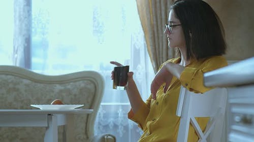 A Brunette Girl in Glasses Sits at a Table and Drinks a Drink From a Glass Quenches Her Thirst