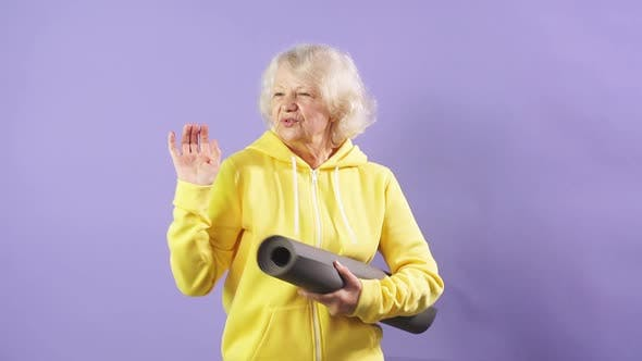 Smiling Mature Model Dancing on Purple Background with Yoga Mat, Good Mood, Happiness Party.