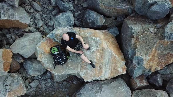 Bald Man lays on a large stone. Tourist with a backpack in shorts and t-shirt is resting.