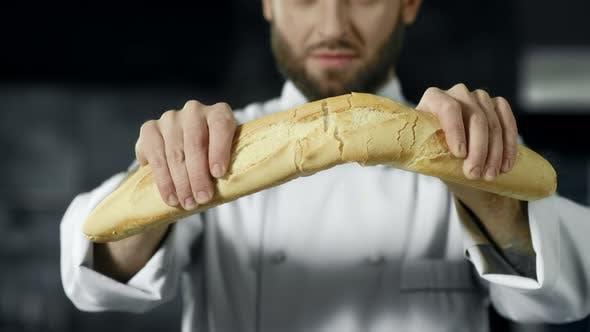 Chef Breaking French Bread in Slow Motion. Closeup Baker Hands Breaking Bread.