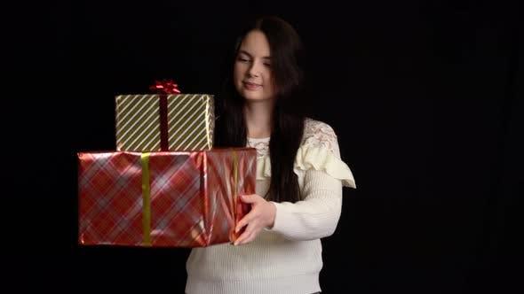 Thumbnail for Junge Frau mit Geschenkbox auf schwarzem Hintergrund, Geschenkbox mit weißem Band für ein glückliches neues Jahr