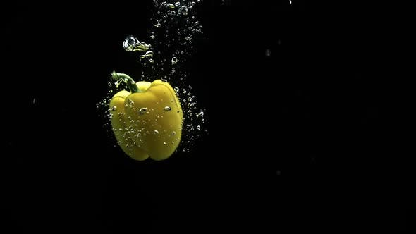 Cover Image for Yellow Bell Pepper Falling In Water And Spinning With Lot Of Air Bubbles Black Background