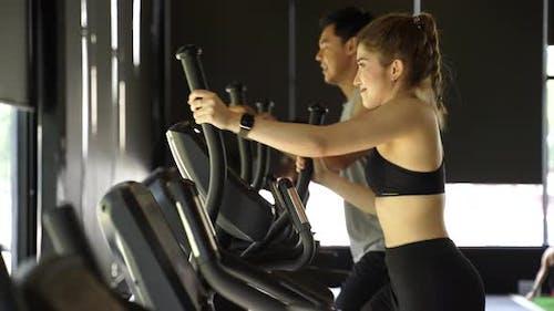 Attraktive asiatische Fitnessfrau mit Ellipsentrainer im Fitnessstudio