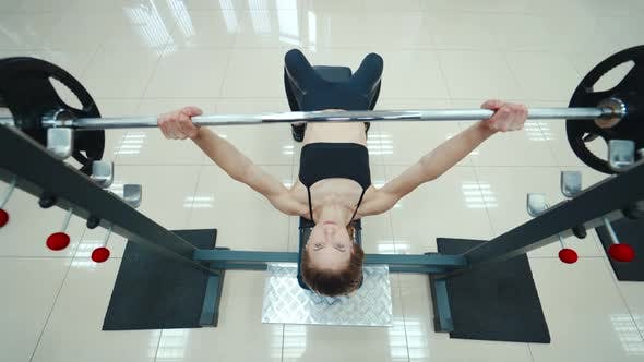 Athletic woman is lying and doing the bench press using the barbell