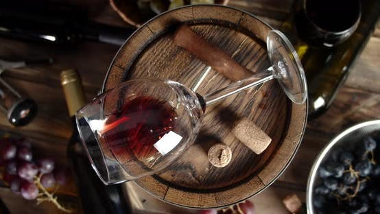 Thumbnail for A Glass of Red Wine Rests on a Barrel. On a Wooden Background.