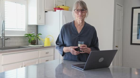 Thumbnail for Senior woman using laptop computer in kitchen while drinking iced coffee