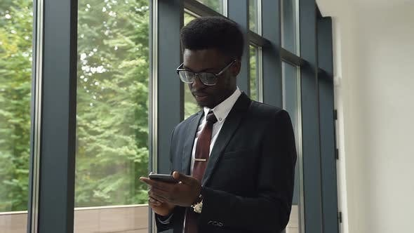 Thumbnail for African american man uses business app on smart phone