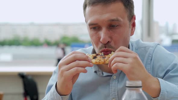 Thumbnail for Handsome Young Man Eating a Slice of Pizza Outside on the Street