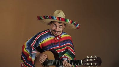 Young Mexican In National Costume Playing Guitar