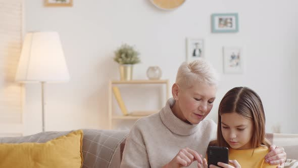 Thumbnail for Caucasian Granny Teaching Girl How to Use Smartphone