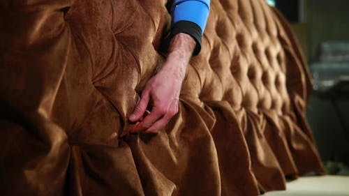 Man Is Straightening Fabric on a Sofa in a Workshop of Assembling of Furniture