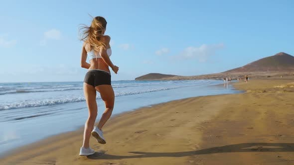 Thumbnail for Beautiful Sporty Women in White Sneakers Running Along a Beautiful Sandy Beach, Healthy Lifestyle