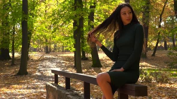 Thumbnail for Eine junge asiatische Frau sitzt auf einem hölzernen Geländer in einem Park und schlägt Posen für eine Kamera