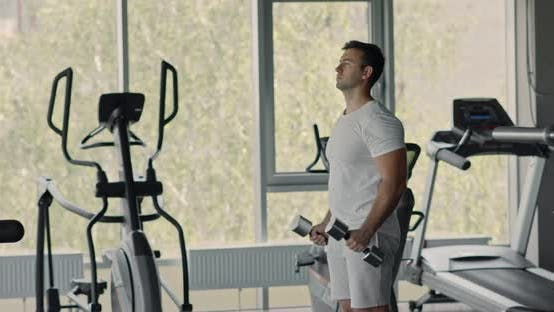 Junger Mann Workout mit Hanteln im Fitnessstudio Interior, Bizeps Workout