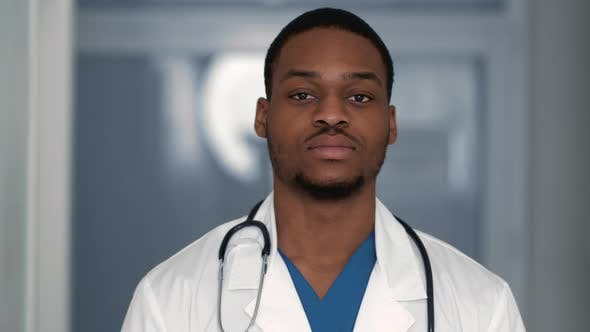Close Up of Confident African American Doctor Looking Seriously at Camera Posing at Clinic Interior