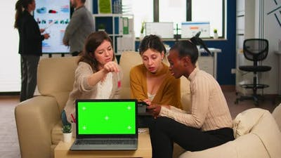 Businesswomen Discussing in Back of Laptop with Greenscreen