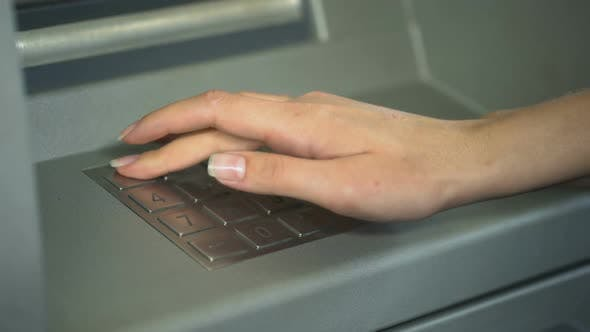 Woman Entering PIN Number to Check Bank Account and Withdraw Money From ATM