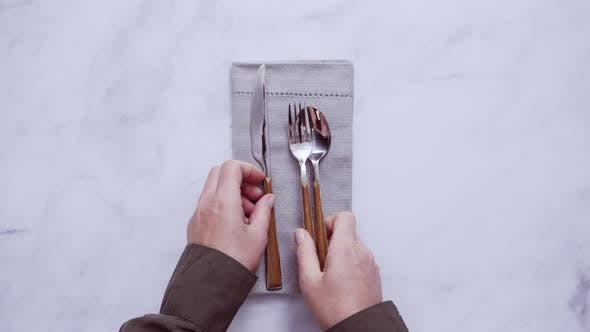 Dinner silverware on linen dinner napkin.