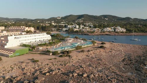 Establisher Shot of an Empty Swimming Pool at Resort Surrounded By Rocky Road and Ocean with Parked