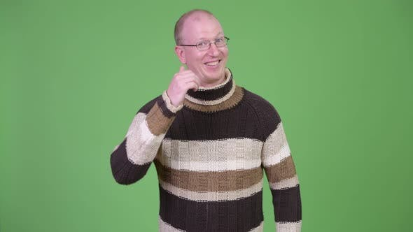 Thumbnail for Happy Mature Bald Man with Turtleneck Sweater Giving Thumbs Up