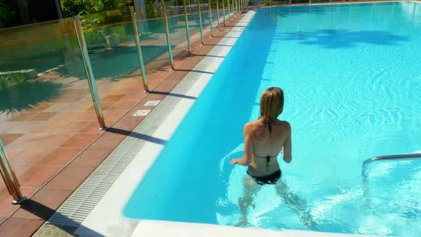 Thumbnail for Beautiful Woman in Bikini Walking on the Side of the Pool Then Swims Afterwards
