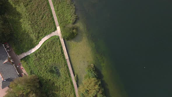 A Top Down Flight over Wooden Decking next to a Large Lake