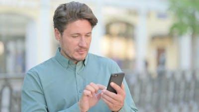 Outdoor Man Browsing on Smartphone