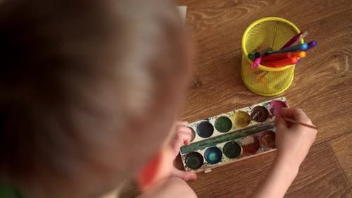A Child on the Floor Draws a Drawing with Watercolors