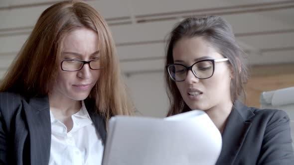 Thumbnail for Konzentrierte Geschäftsfrauen arbeiten mit Papieren
