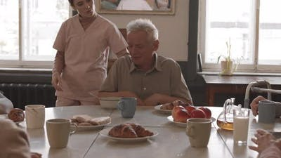 Nurse Feeding Old Man in Nursing Home
