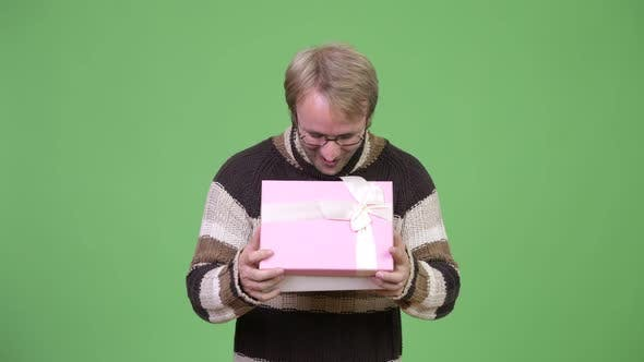 Thumbnail for Studio Shot of Happy Handsome Man Opening Gift Box and Looking Surprised