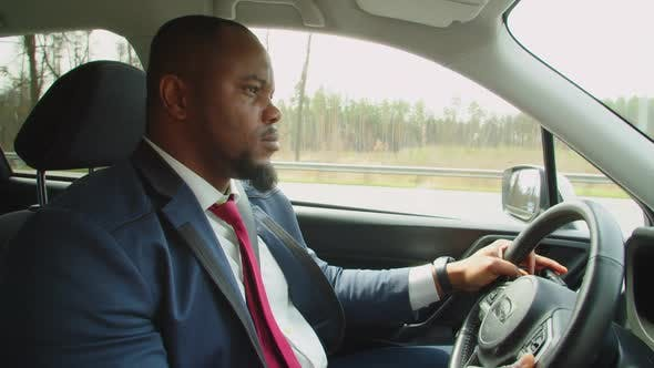 Side View of African Businessman Driving Car on Highway