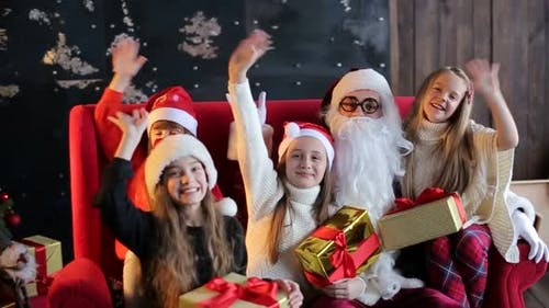 Generous Santa Claus with a group of children holding gifts in their hands