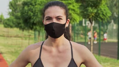 Female Jogger with a Medical Mask on the Face