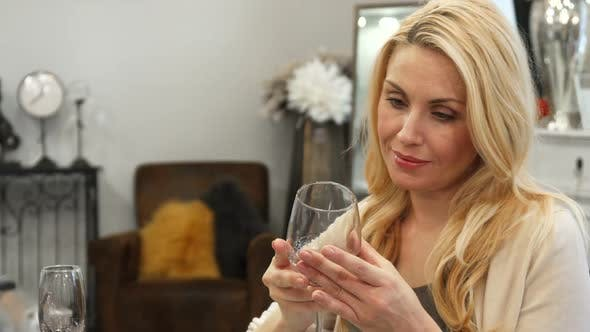 Blonde Woman Chooses a Glass for Wine