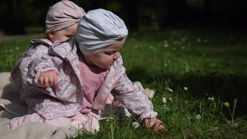 Two Twin Sisters Toddlers in Cute Turbans Sitting in a Blanket in the Park and Playing Curiously