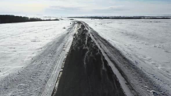 Cover Image for Flight at Low Altitude Over the Winter Road. Wind Overtakes the Snow Across the Road