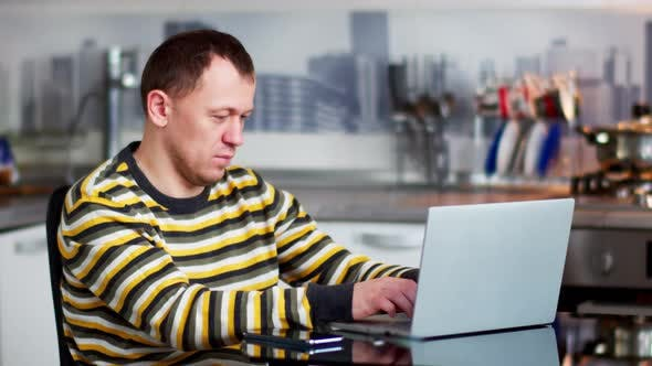 Male Freelancer Working on Laptop at Home While Sitting at Table, Kitchen Background